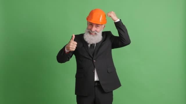 vídeos de stock, filmes e b-roll de empresário de adulto barbudo mostrando uma técnica de segurança sobre um fundo verde - 50 59 years