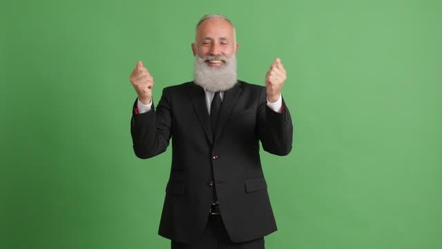 vídeos de stock, filmes e b-roll de empresário de adulto barbudo mostrando cópia espaço no plano de fundo verde - 50 59 years