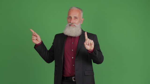 skäggiga vuxen affärsman visar på kopia utrymme och visar ett förbud - 50 59 years bildbanksvideor och videomaterial från bakom kulisserna