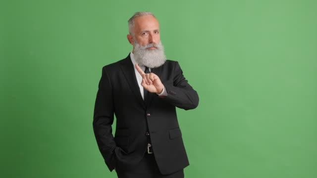 vídeos de stock, filmes e b-roll de empresário de adulto barbudo mostrando no espaço de cópia e mostrando uma proibição - 50 59 years