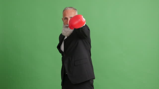Bearded adult businessman strikes against a green background
