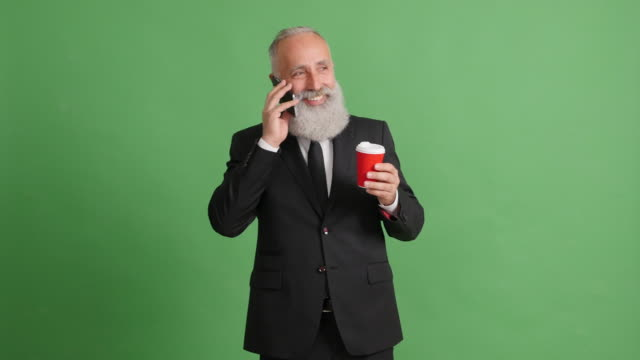 vídeos de stock e filmes b-roll de bearded adult businessman talking on a smartphone on a green background - cabelo grisalho