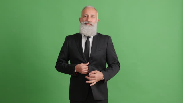Bearded adult businessman unbuttoning his suit and smiling