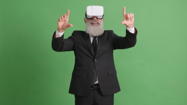 vídeos de stock, filmes e b-roll de barbudo adulto em óculos de realidade virtual em uma tela verde - 50 59 years