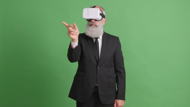 Bearded adult in virtual reality glasses on a green screen