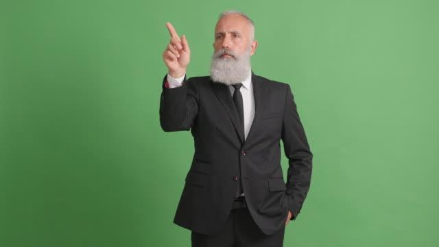 bärtige erwachsenen verwaltet seine hände auf eine kopie des raumes auf einem grünen bildschirm - 50 59 years stock-videos und b-roll-filmmaterial