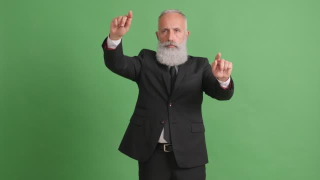 ひげを生やした大人が緑色の画面上の領域のコピーに手を管理します。 - 50 59 years点の映像素材/bロール