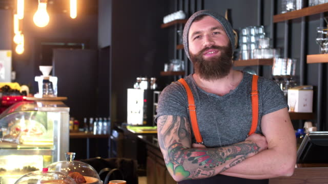 Bärtige und tätowierte Hipster-Kaffee Shop-Betreiber posiert