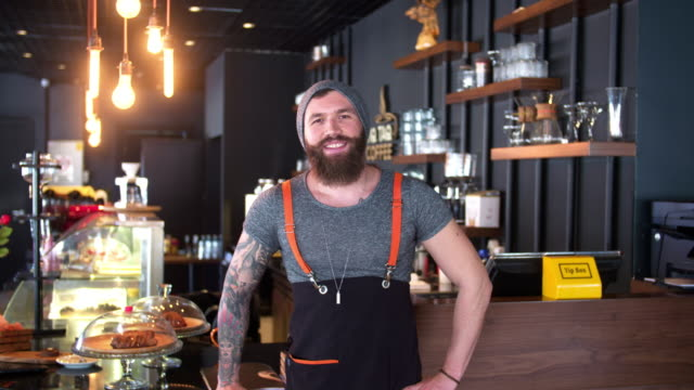 bearded and tattooed hipster coffee shop owner posing - barista stock videos and b-roll footage
