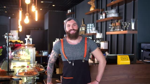 vídeos de stock, filmes e b-roll de dono de loja de café hipster barbudo e tatuado posando - barista