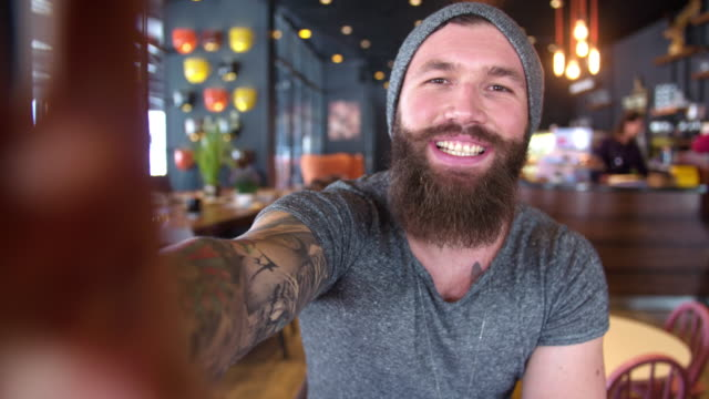 Bearded and tattooed hipster video-calling