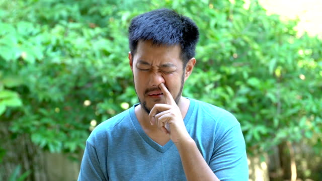 Bearded Asian man pick his nose