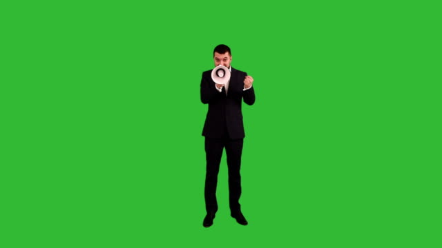 bearded businessman angry and screaming into a megaphone on a green background - megaphone stock videos & royalty-free footage