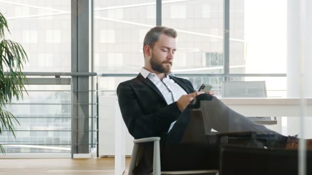 bearded businessman checking smart phone in office lobby - peluria del viso video stock e b–roll
