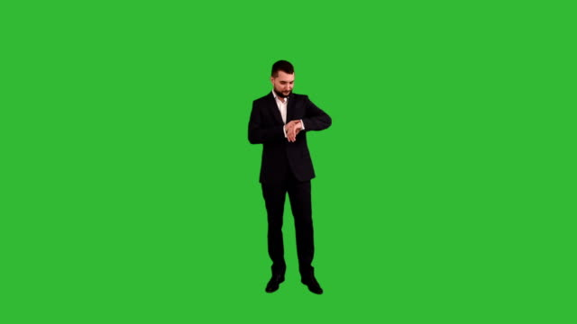 bearded businessman impatiently waiting for gestures and shows a lack of time on the green background