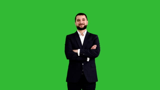 bearded businessman is smiling and looking directly at the camera on a green background