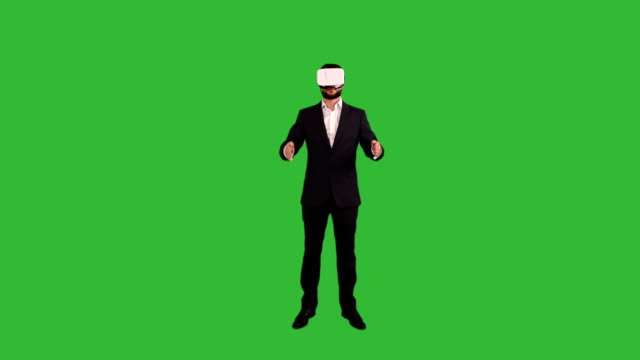 bearded businessman showing a copy space in the virtual reality glasses on a green background