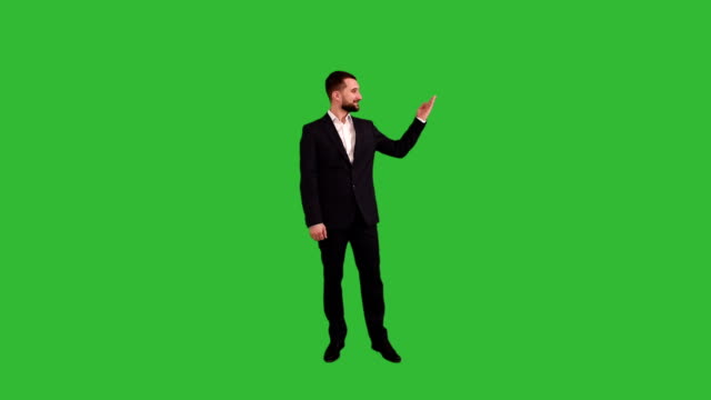 bearded businessman showing a copy space  on a green background