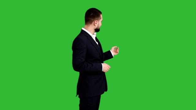 bearded businessman shows something on a green background. back view - standing stock videos & royalty-free footage