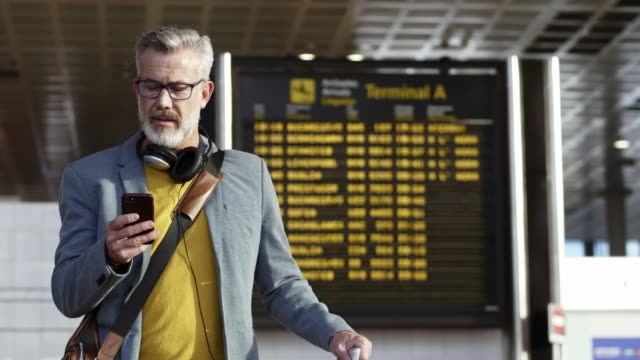 vídeos de stock e filmes b-roll de bearded businessman talking on phone at airport - homens adultos