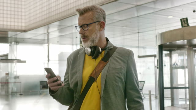 bearded businessman using smart phone at airport - 50 54 years stock videos & royalty-free footage