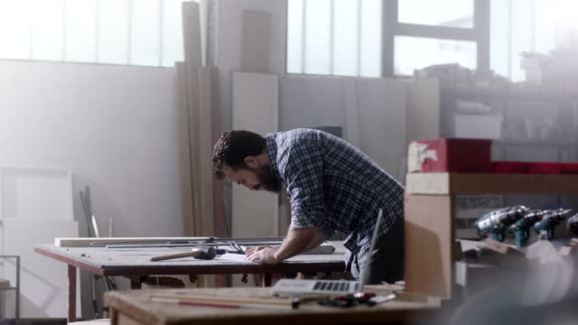 Bearded carpenter drawing and writing on working table at workshop