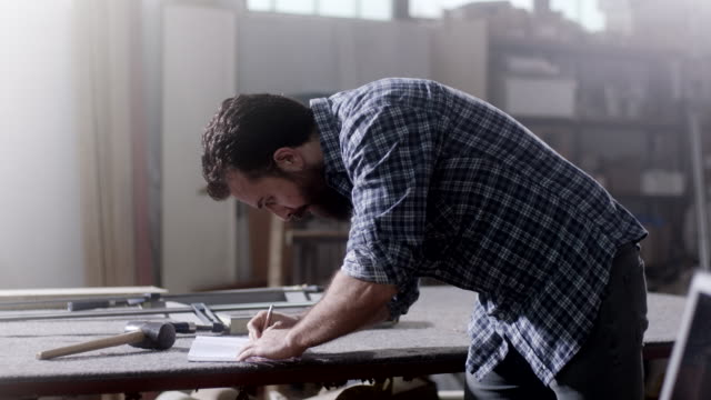 bearded carpenter drawing and writing on working table at workshop - construction worker stock videos and b-roll footage