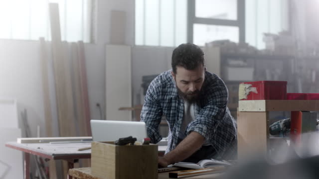 bearded carpenter researching on internet using laptop on working table at workshop - artigiano video stock e b–roll