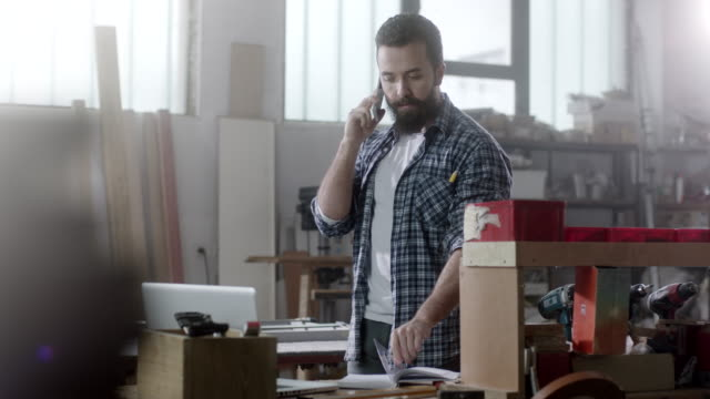 bearded carpenter talking on the phone at workshop - small stock videos & royalty-free footage