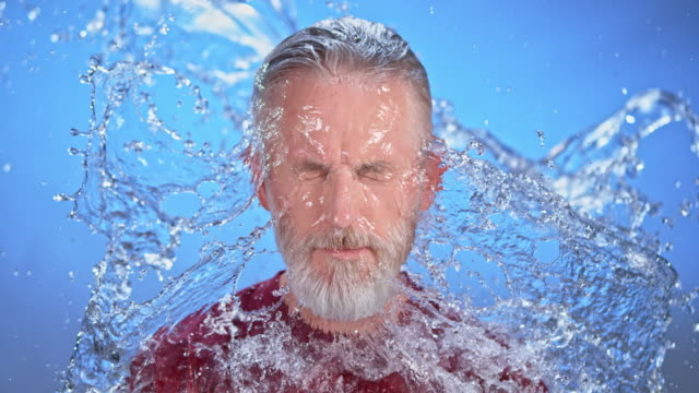 SLO MO LD Bearded Caucasian man being hit with splashes of water from the front
