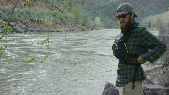 a bearded caucasian man in his twenties with a backwards baseball cap tightens his pfd (personal floatation device) as he stands next the colorado river in colorado - baseball cap stock videos & royalty-free footage