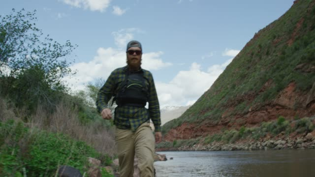 a bearded caucasian man in his twenties with a backwards baseball cap and a pfd (personal floatation device) walks along the colorado river in western colorado - baseball cap stock videos & royalty-free footage