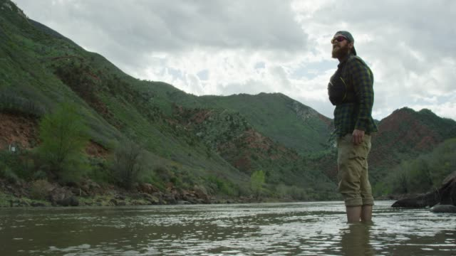 a bearded caucasian man in his twenties with a backwards baseball cap and a pfd (personal floatation device) wades into the colorado river in western colorado under an overcast sky - baseball cap stock videos & royalty-free footage