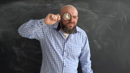 A bearded Caucasian man stands near a school board holding a magnifying glass in his hands and looks attentively. The concept of looking for something with a magnifying glass.
