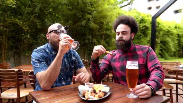 bearded friends enjoying chicken wings and beer at a restaurant - licking stock videos & royalty-free footage