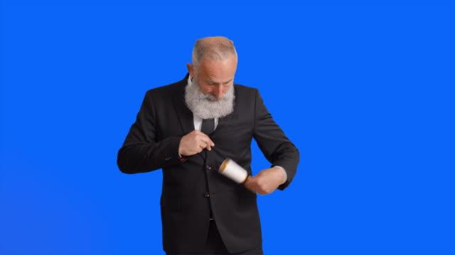 ひげを生やした白髪ビジネスマンのスーツをクリーニング - ワーキングシニア点の映像素材/bロール