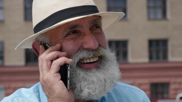 vídeos y material grabado en eventos de stock de hombre con canas barba habla por teléfono - t mobile