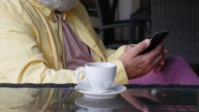 a bearded gray-haired man writes a message on a smartphone and drinks coffee in a cafe - cinquantenne video stock e b–roll