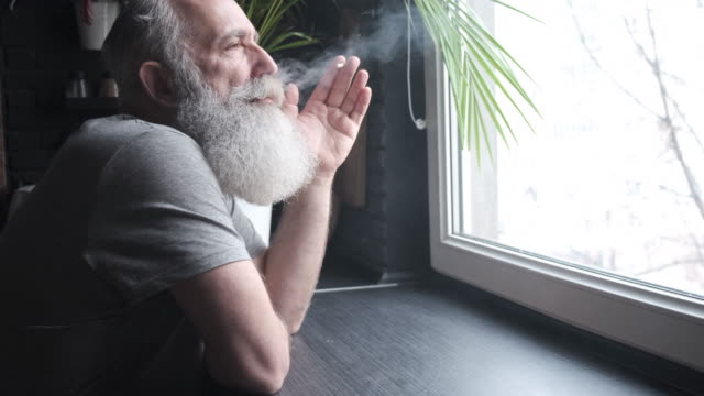 a bearded gray-haired old man looks out the window and smokes in the kitchen - cigarette stock videos & royalty-free footage
