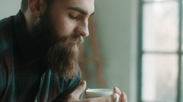 bearded hipster man drinking coffee at atelier - caffè bevanda video stock e b–roll
