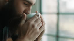 Bearded hipster man drinking coffee at atelier