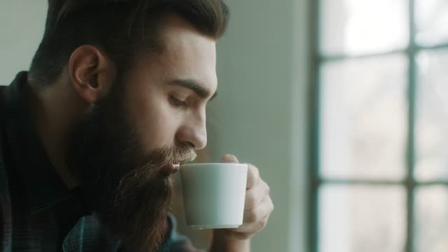 bearded hipster man drinking coffee at atelier - drinking stock videos and b-roll footage