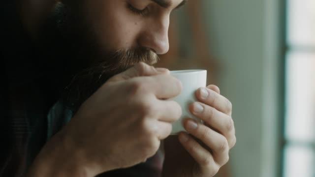 bärtige hipster mann kaffeetrinken im atelier - vollbart stock-videos und b-roll-filmmaterial