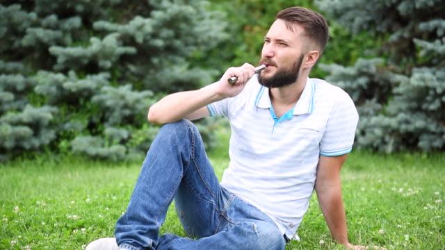 bärtiger hipster, raucht eine elektronische zigarette. - snuff stock-videos und b-roll-filmmaterial