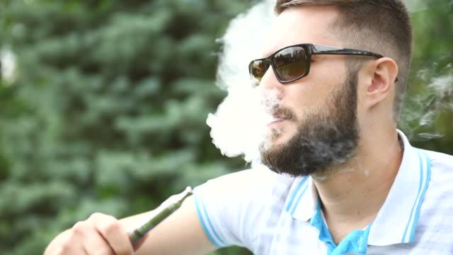 vídeos de stock e filmes b-roll de hipster barbudo fumar um cigarro eletrónico. - condensação