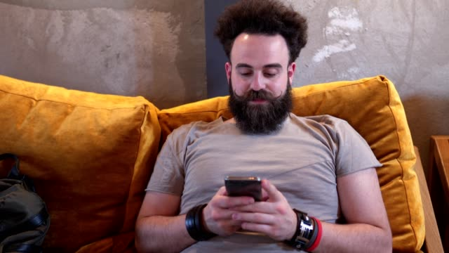 bearded hipster texting at a cafe - barba peluria del viso video stock e b–roll