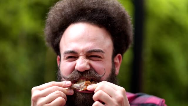 vídeos de stock e filmes b-roll de bearded hipster with a pointy mustache eating a chicken wing - carne