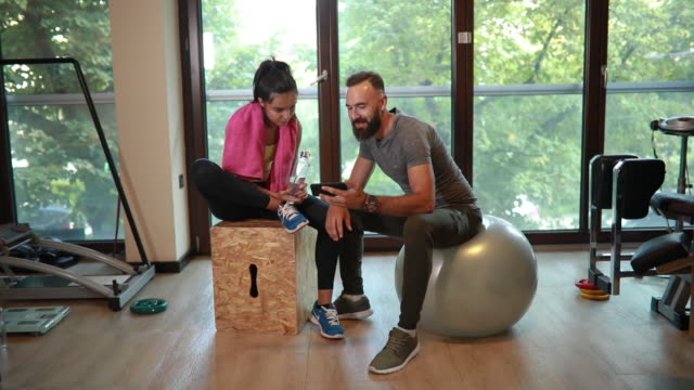 bearded instructor showing workout plans to a young athletic woman - comment box stock videos & royalty-free footage