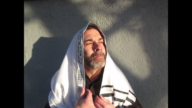 bearded jewish man wearing a yamaka and standing against the white wall director directing his movement during a take he takes his shawl off and puts... - shawl stock videos & royalty-free footage