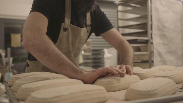 bearded male baker preparing sourdough bread before baking in oven wearing apron in bakery - beard stock videos & royalty-free footage